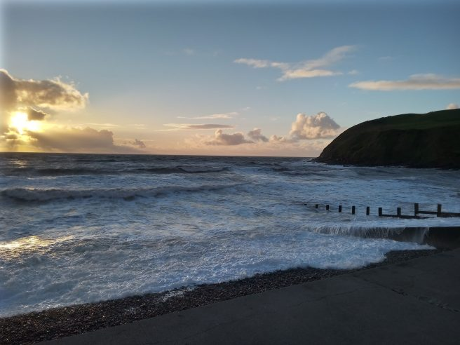 Seascape with sunlit clouds and headland